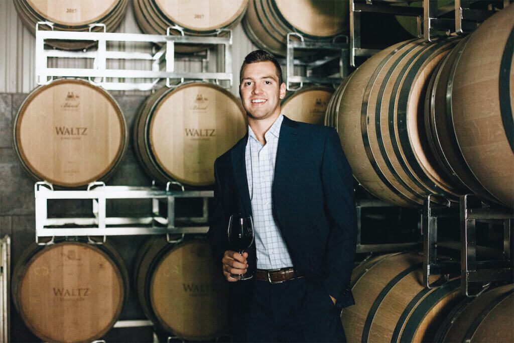 zach waltz standing in front of wine barrels holding a glass of wine